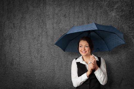 executive affable: Friendly businesswoman hide and protect herself under umbrella.
