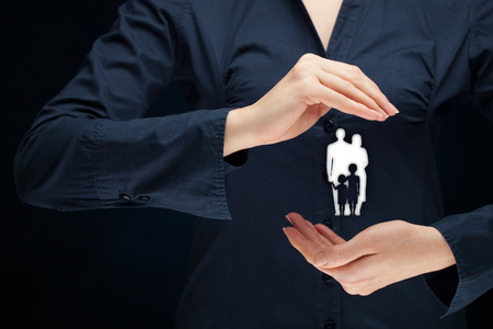 family policy: Family life insurance, family services, family policy and supporting families concepts. Woman with protective gesture and silhouette representing young family.
