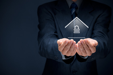 provide: Property security concept. Offering gesture of man and symbol of house with padlock. Stock Photo