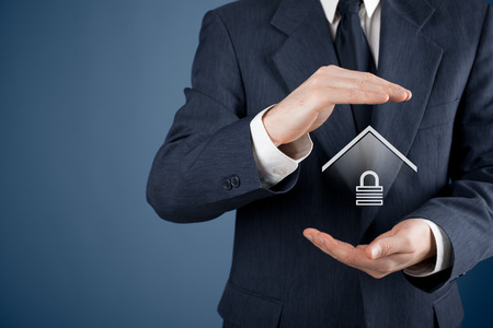 residential housing: Property security  concept. Protecting gesture of man and symbol of house with padlock.
