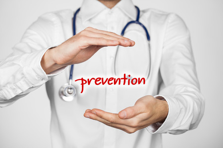 general practitioner: Healthcare prevention doctor (general practitioner) concept. Doctor with protective gesture and text prevention.