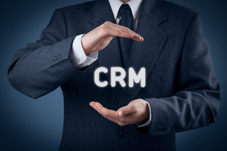 protective shield: CRM (customer relationship management) concept. Businessman with protective gesture and text CRM.