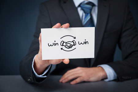 Win-win partnership strategy concept. Businessman with drawn win-win scheme on card and handshake partnership agreement.