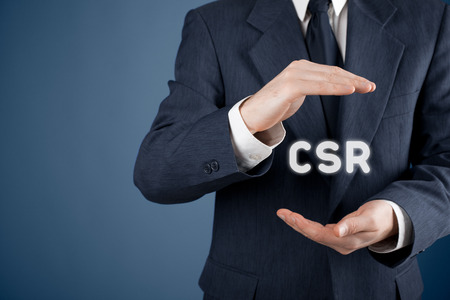 Corporate social responsibility (CSR) concept. Businessman with protective gesture and text CSR 免版税图像