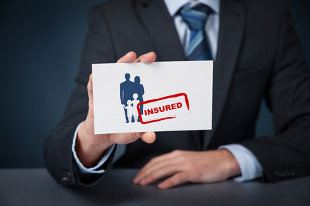 insure: Insured family concept. Insurance agent with family silhouette on card and printed stamp insured. Stock Photo