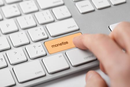 monetization: Monetize on-line internet project concept. Freelancer (e-nomad, digital nomad) revenue his microbusiness startup - click on keypad monetize on keyboard.