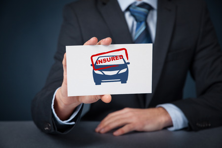 insured: Insured car concept. Insurance agent with car silhouette on card and printed stamp insured.