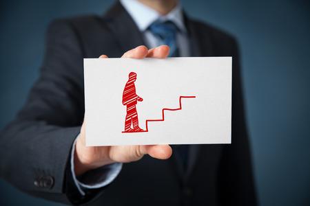superacion personal: Desarrollo personal (crecimiento personal), el �xito, el progreso, conceptos potenciales y de carrera. Entrenador masculino (oficial de recursos humanos, supervisor) con escaleras de tarjetas y elaborados para ayudar a los empleados con su crecimiento profesional. Foto de archivo