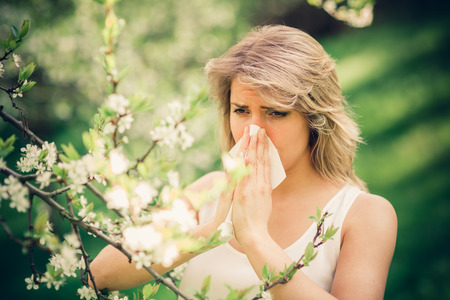 Woman with pollen allergy in springtime near tree in bloom.