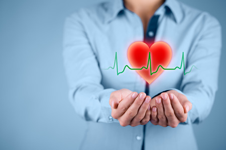 cardiac care: Protect health (healthcare) and heart problems prevention (cardiology) concept. Cardiologist with protective gesture and symbol of heart and ECG heartbeat. Stock Photo