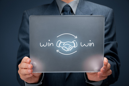 win: Win-win partnership strategy concept. Businessman with drawn win-win scheme and handshake partnership agreement on futuristic tablet computer. Stock Photo