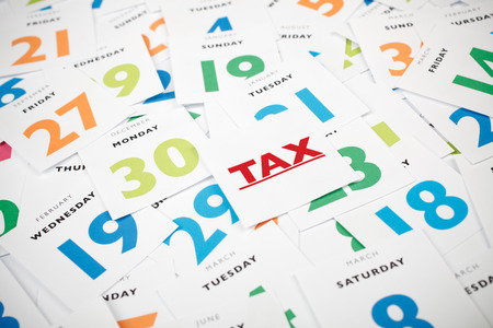 Mention: Remind date of tax payment. Papers with date and one paper with text tax. Stock Photo