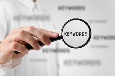 Vind trefwoorden concept. Marketing specialist op zoek naar trefwoorden (concept met vergrootglas). Stockfoto