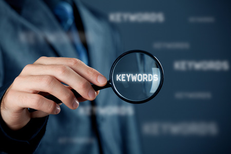 keywords: Find keywords concept. Marketing specialist looking for keywords (concept with magnifying glass).