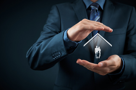 protect family: Insurance concept of family life and property insurance, family services, family policy and supporting families concepts. Businessman with protective gesture and silhouette representing young family and house.
