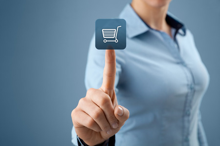 Woman click on virtual e-shop button with shopping cart. E-commerce and B2C concept. Stock Photo