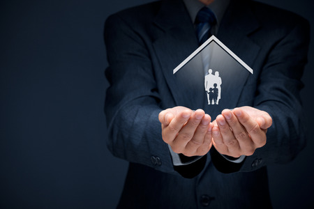 home insurance: Insurance concept of family life and property insurance, family services, family policy and supporting families concepts. Businessman with protective gesture and silhouette representing young family and house.