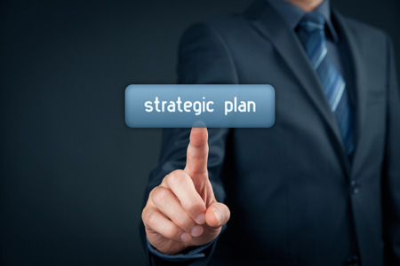 managerial: Businessman click on virtual button with text strategic plan.
