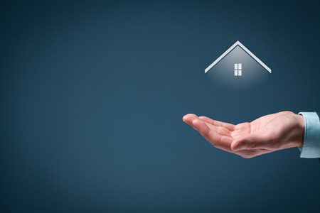 residential homes: Property insurance and real estate agent concept. Care gesture of man and symbol of house. Stock Photo