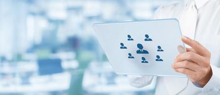Los recursos humanos, auditoría personal, CRM y evaluación concepto de centro - reclutador selecto de empleados (o jefe de equipo) representados por el icono de la tableta futurista. Composición ancha, la oficina en el fondo.
