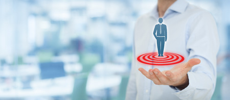 Target customer (marketing) concept. Businessman hold target customer represented by virtual icon of man standing on target. Wide banner composition, office in background. Stock Photo
