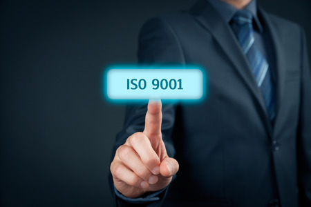 managerial: ISO 9001 - quality management system. Businessman click on button with ISO 9001 - certification concept. Stock Photo