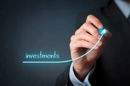 Increase investments concept. Businessman plan (predict) investments growth represented by graph.