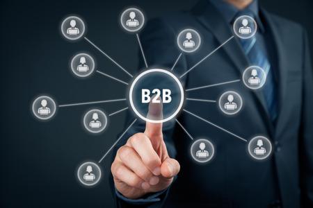 business model: Business-to-business (B2B) - business model. Zakenman op virtuele knop met B2B tekst. Zakelijke partners in verband met de toets. Stockfoto