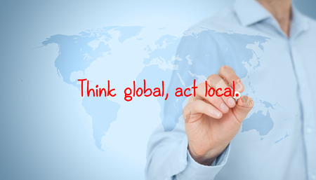Local business: Think global, act local. Globalization business rule. Businessman draw this rule on virtual board. Stock Photo