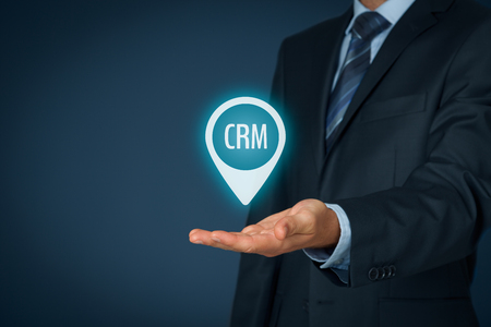 managerial: Customer relationship management (CRM) concept. Businessman hold virtual label with text CRM. Stock Photo