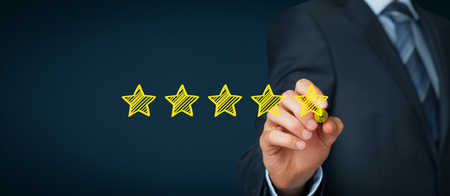 review icon: Increase rating, evaluation and classification concept. Businessman draw five yellow star to increase rating of his company. Wide banner composition. Stock Photo