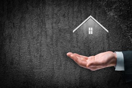 seguro: El seguro de propiedad y el concepto de agente de bienes raíces. Cuidado gesto de hombre de negocios y símbolo de la casa. Foto de archivo