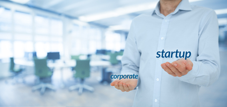 to prefer: Startup versus corporate business concept. Young businessman (or employee) prefer startup company against corporation. Wide banner composition and office in background. Stock Photo