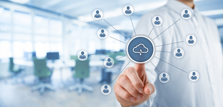 Cloud computing concept - connect office workers to cloud storage. Businessman click on cloud computing icon connected with corporate users working on notebooks with access rights. Wide banner composition with office in background.