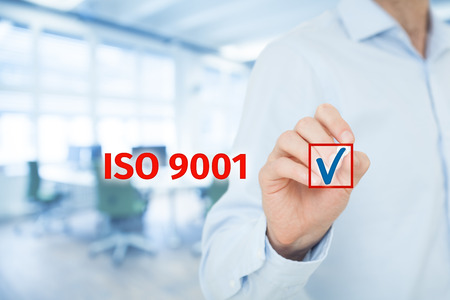 quality: ISO 9001 - quality management system. Businessman select ISO 9001 certification. Wide banner composition with office in background.