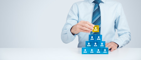 Human resources and corporate hierarchy concept - recruiter complete team by one leader person (CEO) represented by gold cube and icon. Wide banner composition.