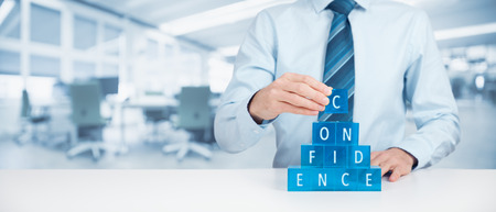 build in: Build confidence - self-confidence improvement concept. Coach or mentor helps build confidence. Wide banner composition with office in background. Stock Photo