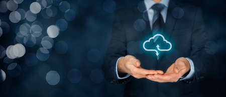 Cloud computing service concept - connect to cloud. Businessman offering cloud computing service represented by icon. Wide banner composition and bokeh in background. Stock Photo