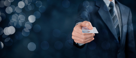 Businessman in business suit pay by credit card. Wide banner composition with bokeh in background.