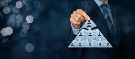 CEO, leadership and corporate hierarchy concept - recruiter complete team represented by puzzle in pyramid scheme by one leader person (CEO). Wide banner composition with bokeh in background. Stockfoto