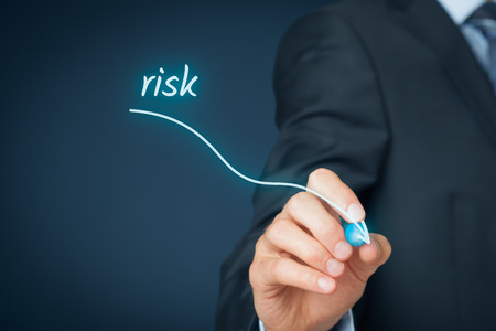 Risk management concept. Businessman (risk manager) draw descending curve in graph to reduce corporate risk. Stock Photo