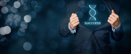 genes: Businessman shows he has genes (talent, natural ability, aptitude) for success in business (represented by DNA symbol). Wide banner composition with bokeh in background.