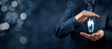 familias jovenes: seguro de vida familiar, los servicios de apoyo a la familia y conceptos familias. Hombre de negocios con gesto protector y la silueta que representa a la familia joven. composición de la bandera de ancho con el bokeh en segundo plano. Foto de archivo