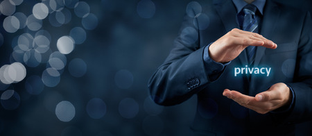 Privacy policy concept. Businessman with protective gesture and text privacy in hands. Wide banner composition with bokeh in background. Stok Fotoğraf