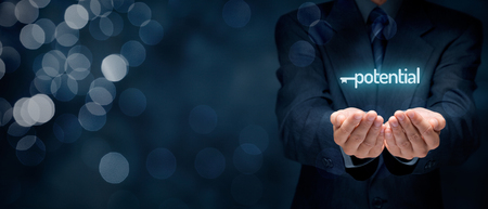 Unlock potentiële - motivationele concept. Zakenman met het symbool van de toets verbonden met tekst potentieel bij de hand. Brede samenstelling van de banner met bokeh op de achtergrond. Stockfoto