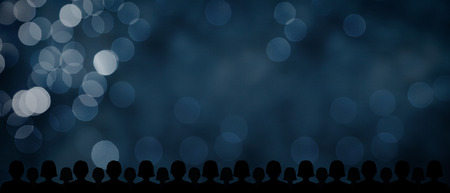 Audience and blue bokeh background with wide banner composition. Background for business and marketing presentations (ideal for target audience, target customer, mass marketing etc.).