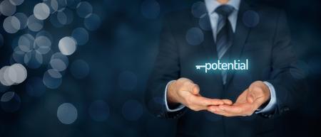 Sbloccare il potenziale - concetto motivazionale. Uomo d'affari con il simbolo della chiave connessa con un potenziale di testo a portata di mano. Ampia la composizione di banner con bokeh in background.