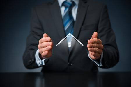 El seguro de propiedad y el concepto de seguridad. La protección gesto de hombre y el símbolo de la casa, la composición central. Foto de archivo