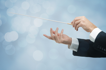 Male orchestra conductor hands, one with baton. Blue background with bokeh.