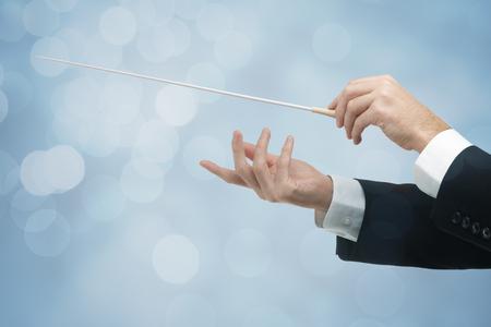 orquesta: Manos del conductor de orquesta de sexo masculino, uno con el bastón. Fondo azul con el bokeh.